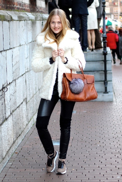 leather pants, sneakers, brown leather bag accessorized with a faux-fur ball