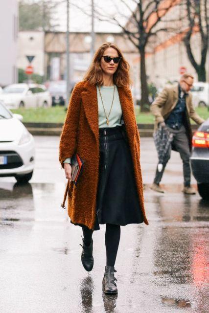 A-line midi skirt, biker ankle boots, simple pastel blouse, cat-eye sunglasses, clutch